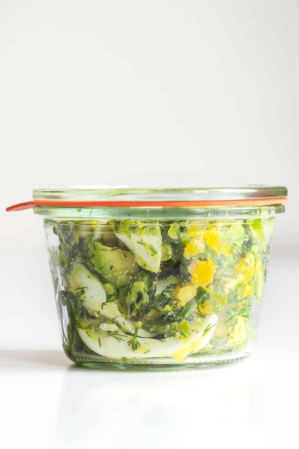 Avocado Egg Salad in a meal prep glass container with lid on.