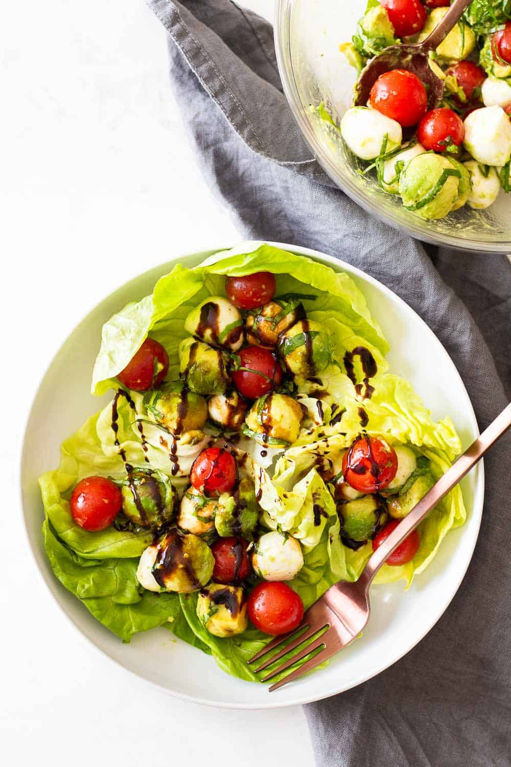 Tomato Avocado Salad served in butter lettuce leaves on a white plate.