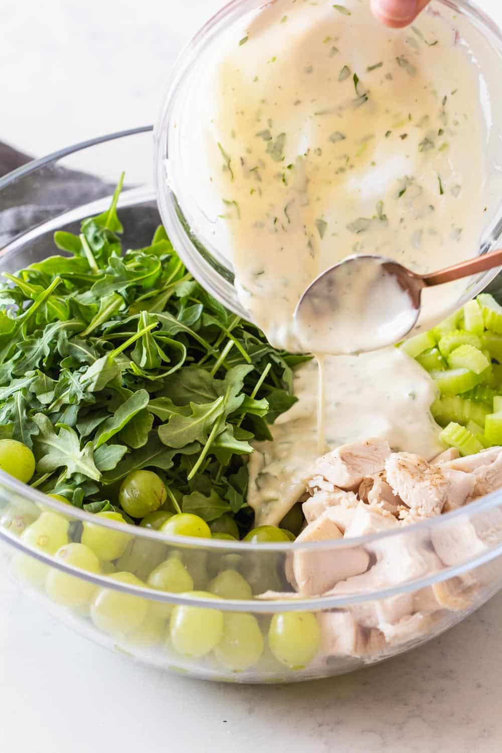 Yogurt Dressing being poured over Chicken Salad Recipe with Grapes