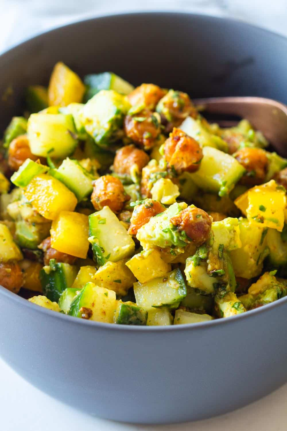 Mixed up Cucumber Avocado Salad in a small grey bowl