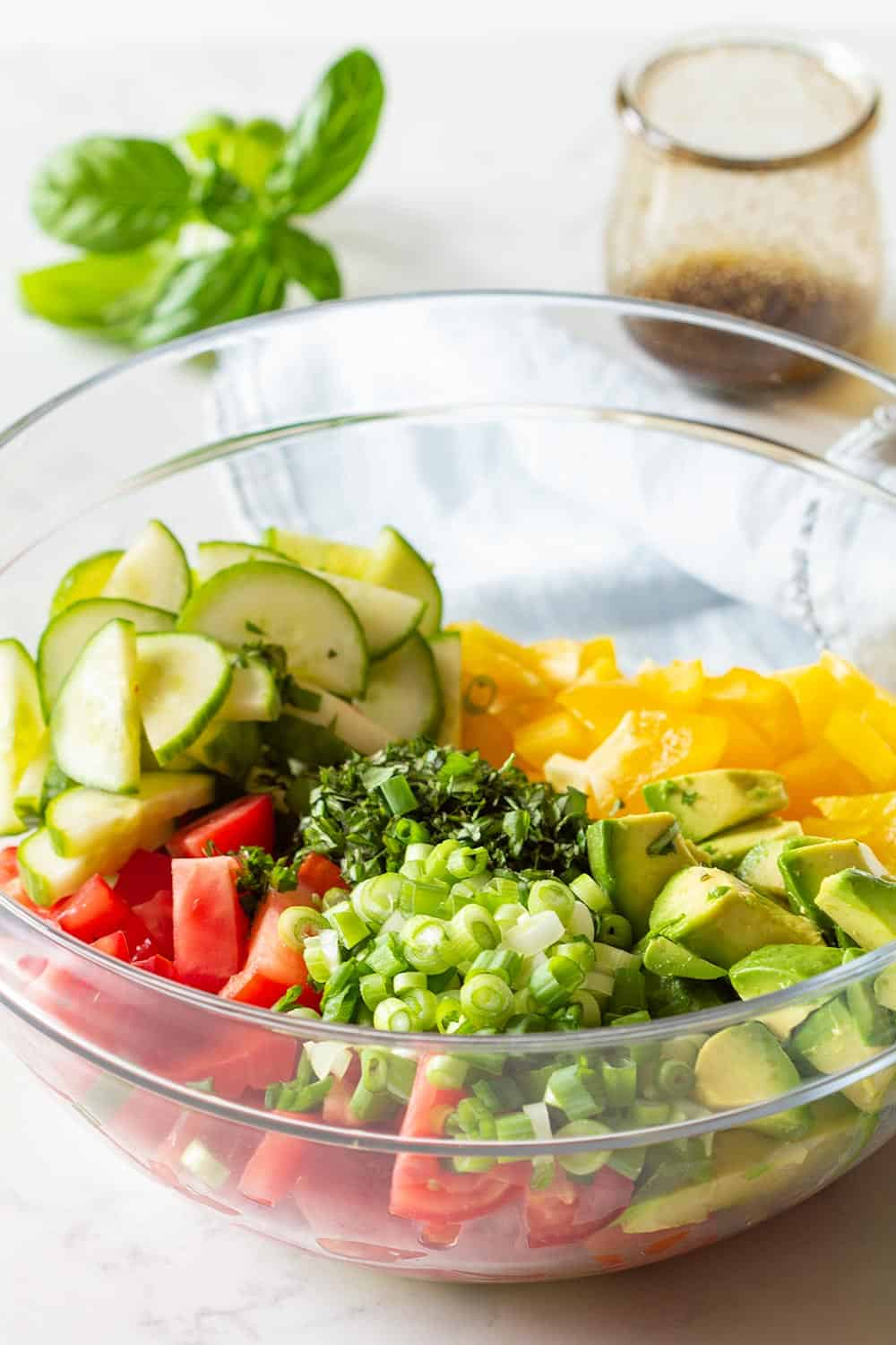 Cucumber Tomato Avocado Salad Recipe in a glass bowl and balsamic vinaigrette in a separate glass jar