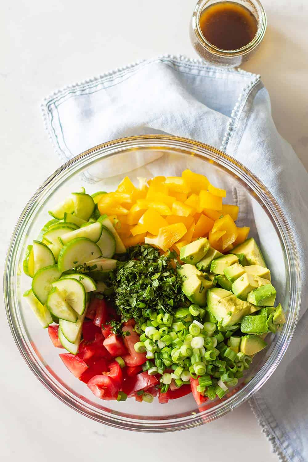 Cucumber Tomato Avocado Salad ingredients in a large glass bowl and balsamic vinaigrette in a separate glass jar