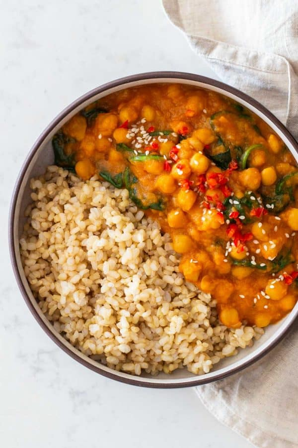 Sweet Potato Curry with chickpeas and baby spinach made in Instant Pot served with brown rice in a round bowl.