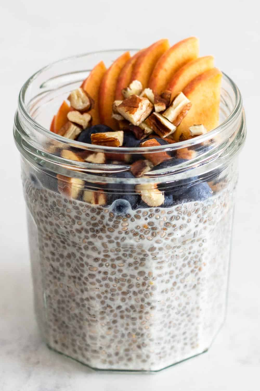 Vanilla-flavored almond milk Chia Seed Pudding in a glass jar topped with peach, blueberries and pecans.
