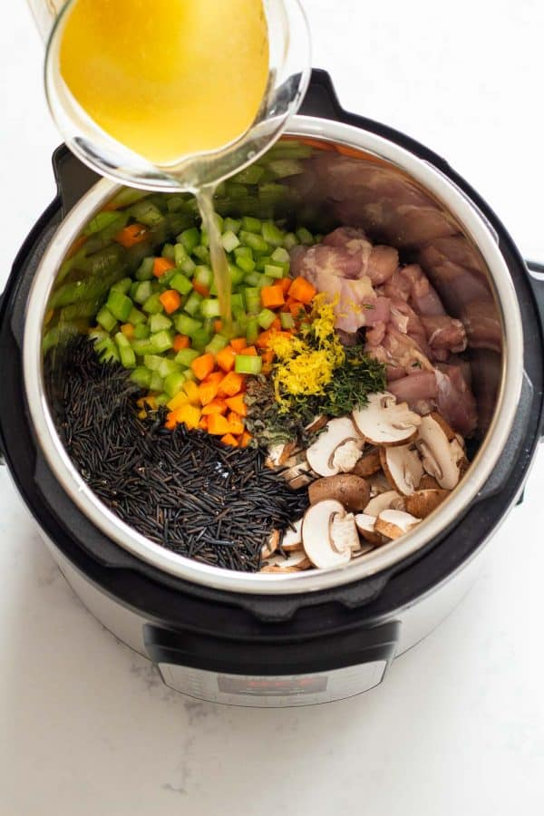 Instant Pot Chicken Wild Rice Soup Ingredients shown in the pressure cooker and pouring in broth.