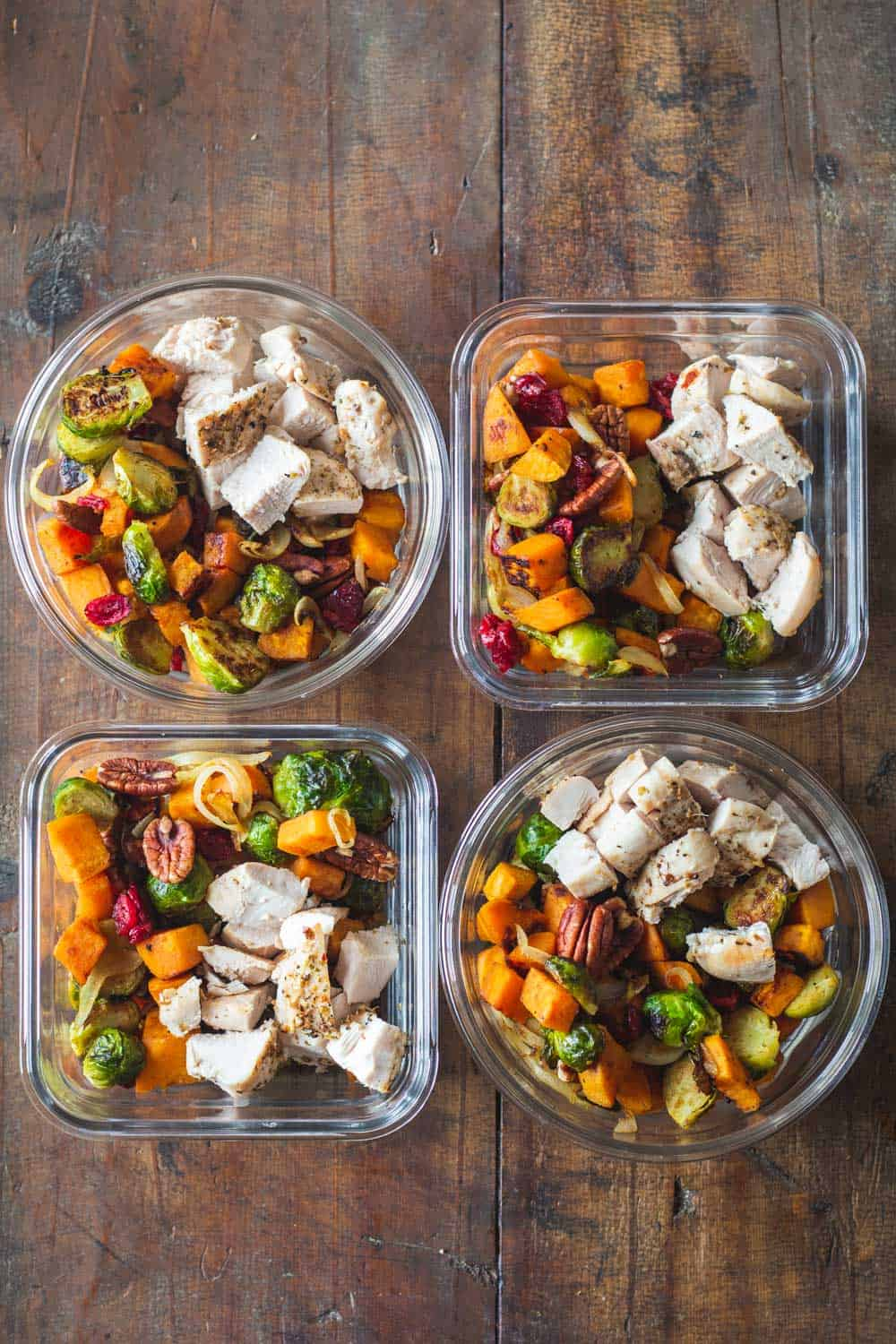 Four Maple Dijon Chicken Meal Prep Bowls on a wooden table.