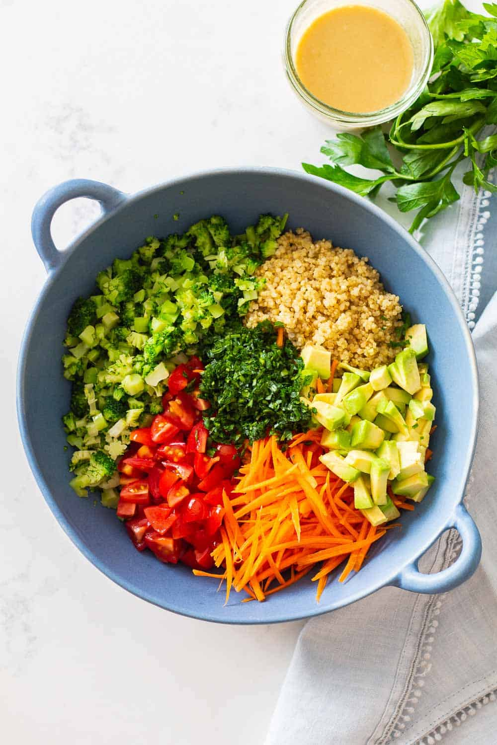 Quinoa salad with broccoli, carrot, tomato, avocado, parsley in a blue bowl.