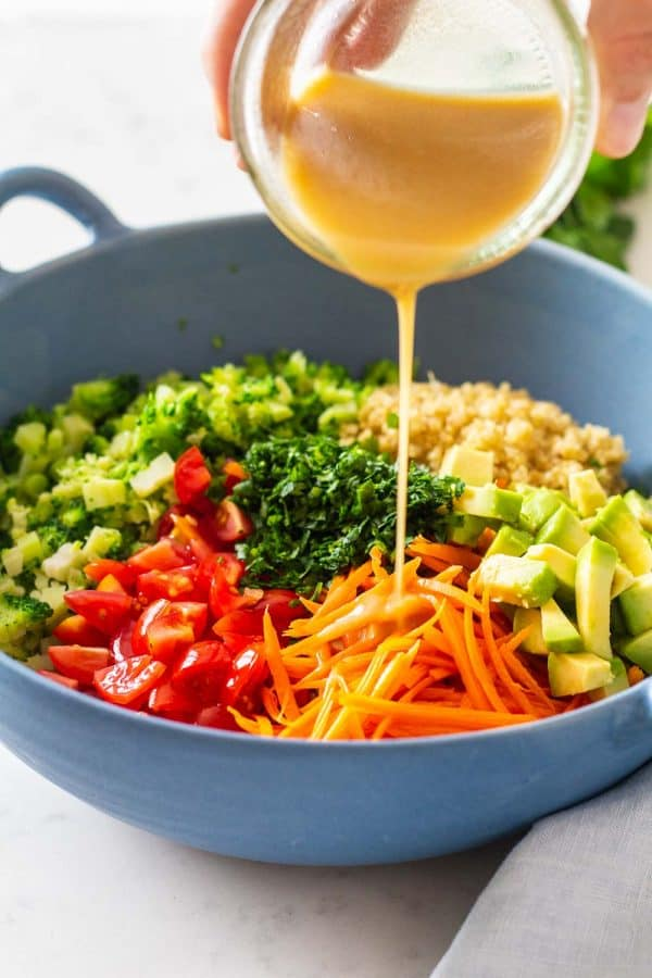 Pouring honey mustard dressing over quinoa salad