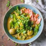 Thai Curry Soup in a blue bowl showing shredded salmon, potatoes, broccoli, and snow peas in broth on a wooden table