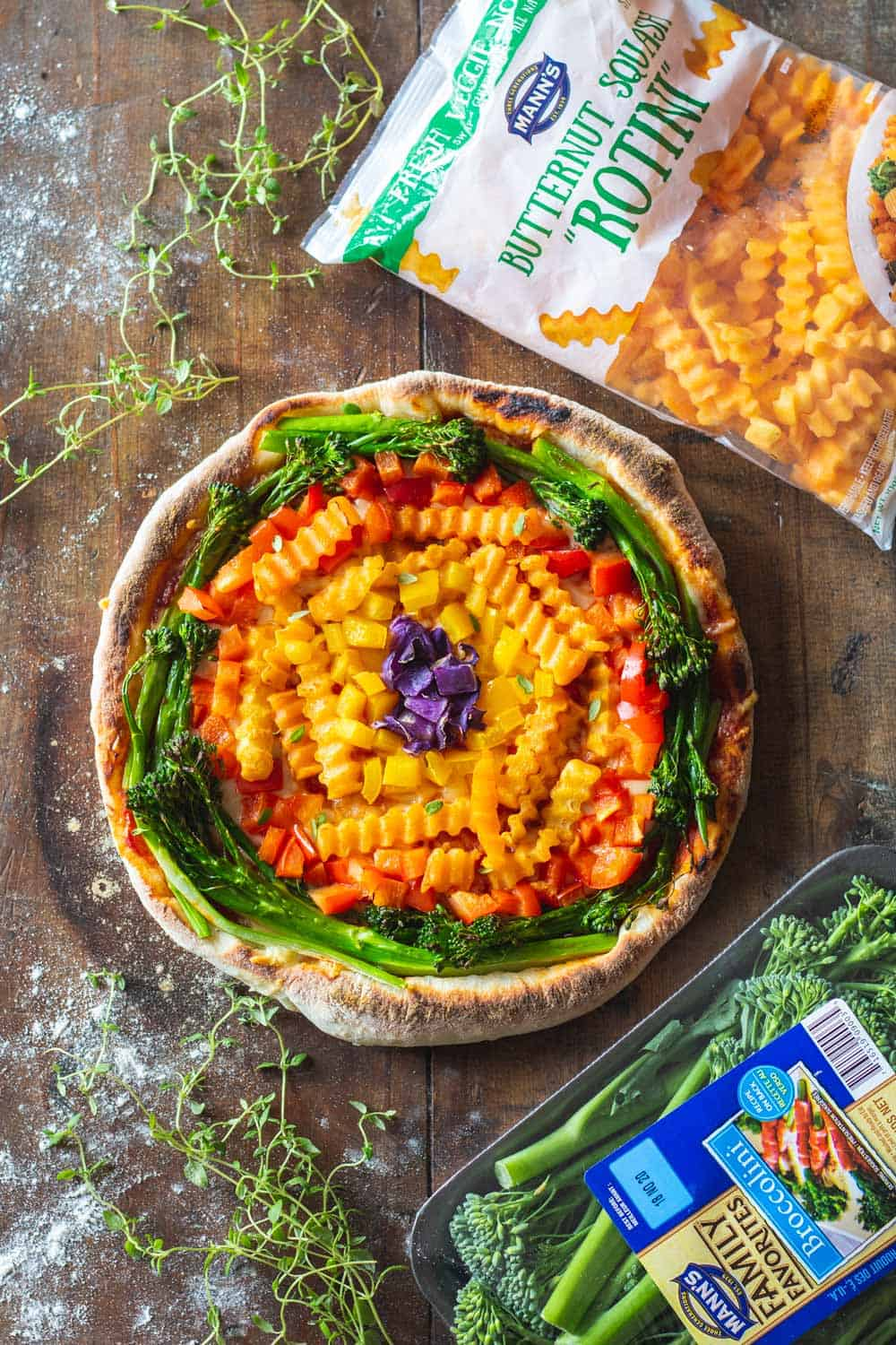 Mann's Broccolini and Mann's Butternut Squash Rotini Bags around rainbow pizza