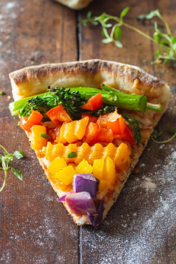 A piece of authentic Italian veggie pizza with veggies of the colors of the rainbow.