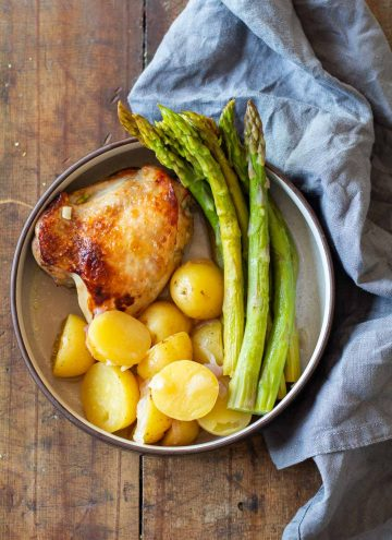 Instant Pot Lemon Chicken on a plate with potatoes and asparagus