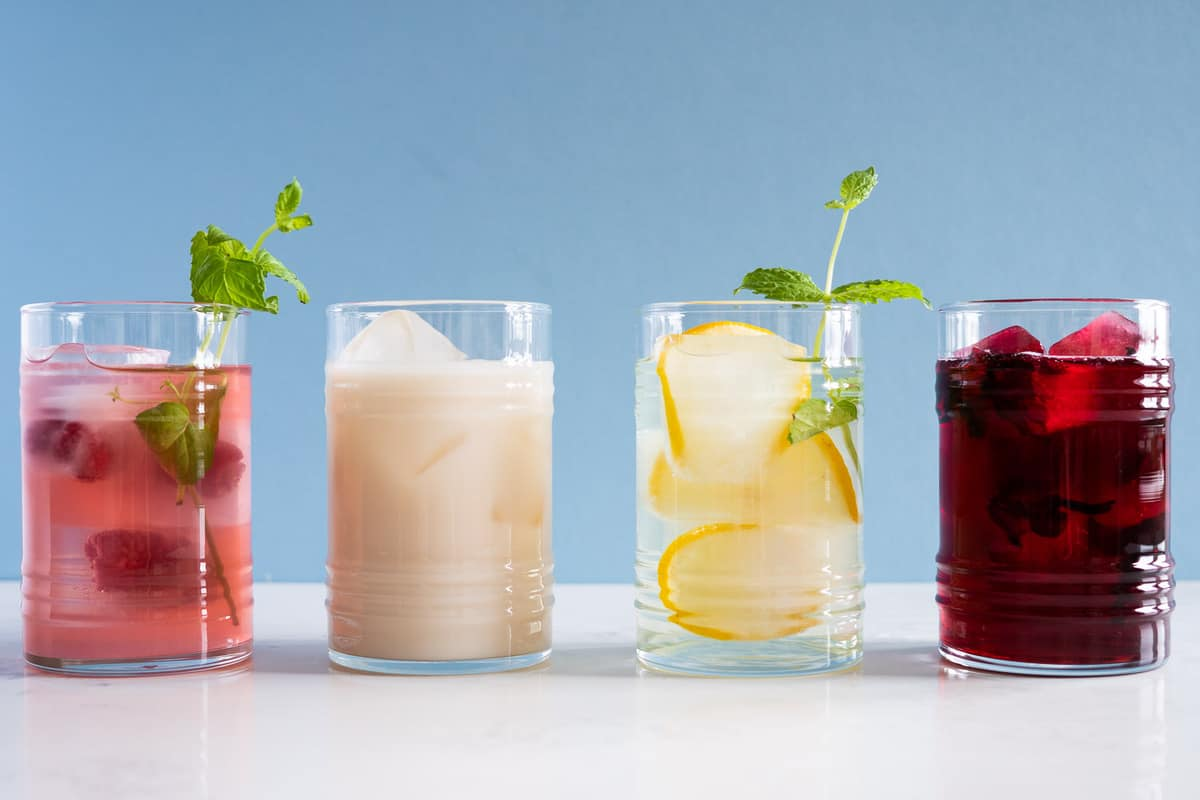 4 summer drinks - in drinking glasses - hibiscus tea, pink lemonade, agua de horchata, and lemon infused water