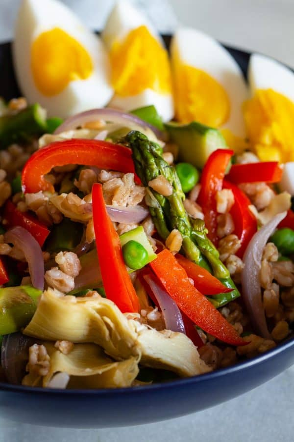 healthy spring salad with spring vegetables, hard boiled egg wedges, and farro