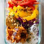 Chicken Satay Skewers on raw vegetables and rice noodles with peanut sauce