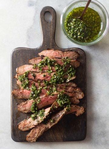 Flank Steak on a cutting board and Chimichurri in a jar