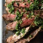 Sliced Flank Steak with Chimichurri on a cutting board
