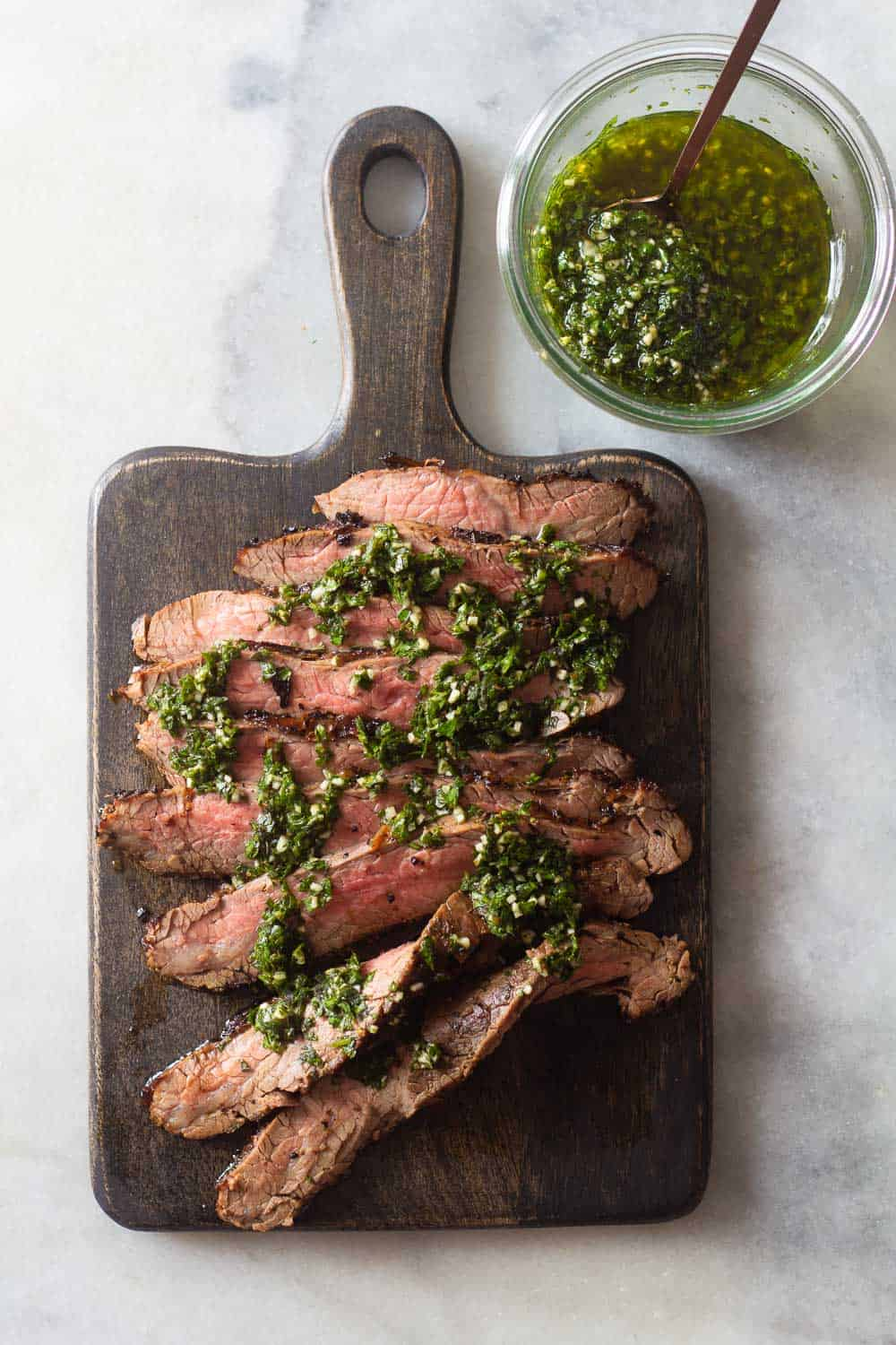 Flank Steak on a cutting board and Chimichurri in a jar