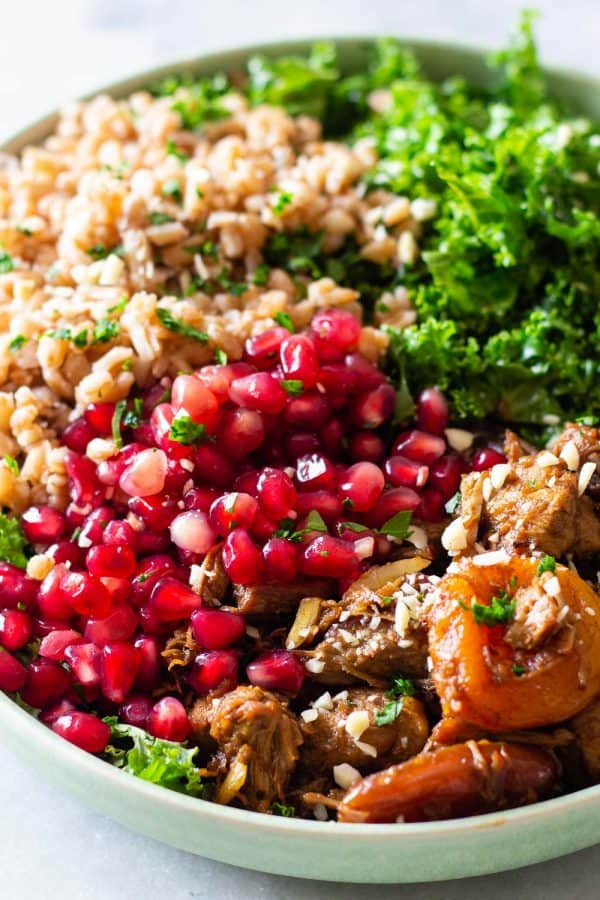 big bowl of farro salad with kale and pomegranate seeds