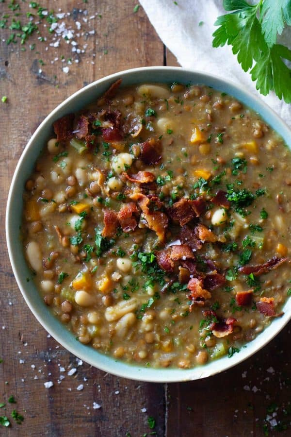 Crockpot Lentil Soup in a blue bowl topped with bacon