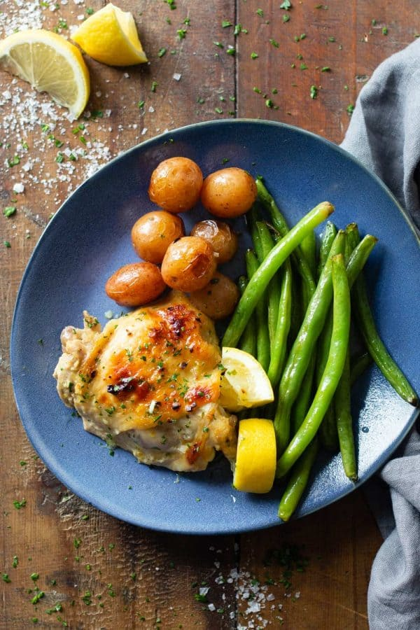 Lemon Garlic Chicken Thigh on a blue plate with potatoes and green beans