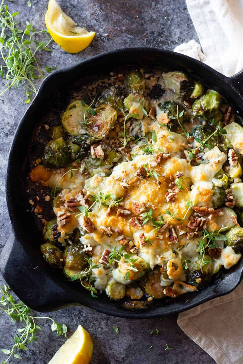 Brussels Sprouts in a black cast iron pan with melted cheese on top