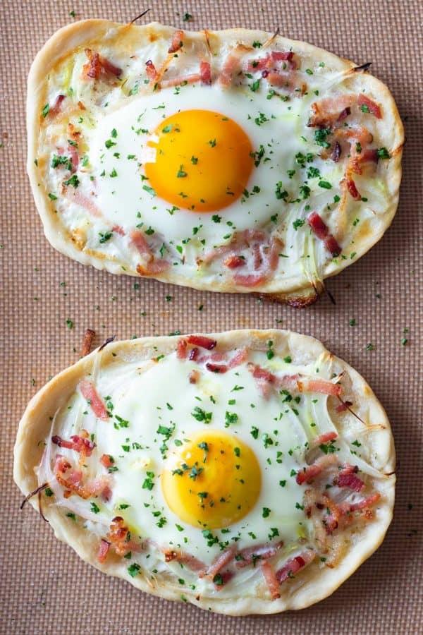 Two breakfast pizzas on a baking sheet
