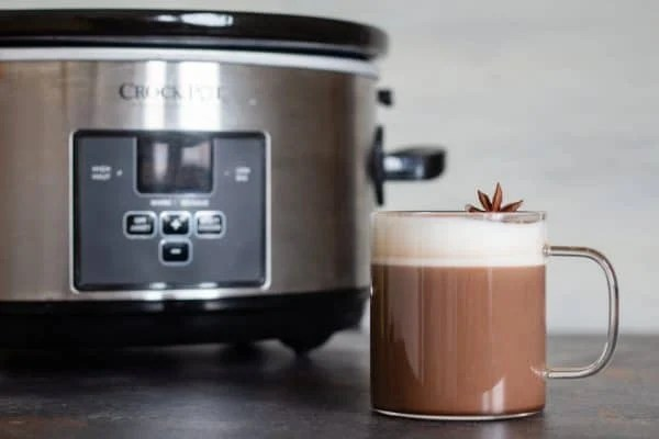 Mexican spiced hot chocolate in a cup in front of a Slow-Cooker