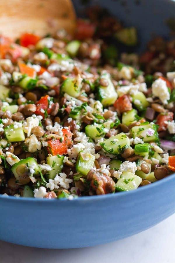 mixed up lentil salad in a blue bowl
