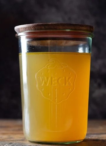 Golden chicken bone broth in a glass jar with wooden lid on top