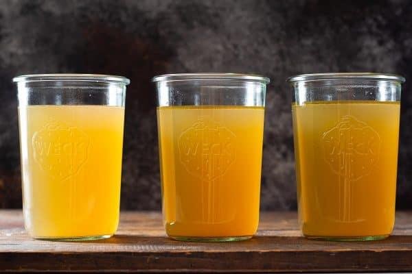 Three glass jars filled with golden chicken bone broth