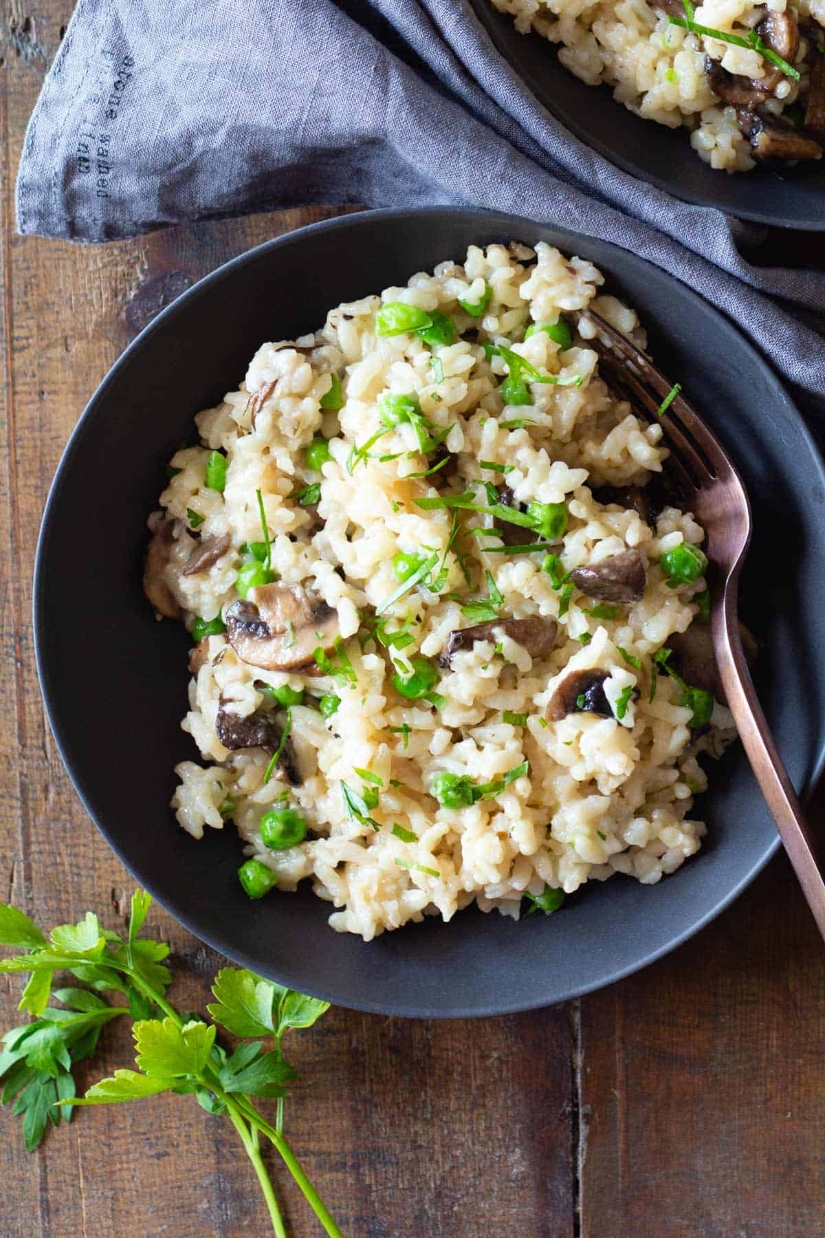Mushroom and Pea Risotto in a grey bowl on a wooden table