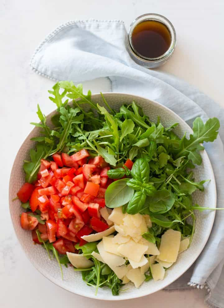 arugula, diced tomato, and shaved parmesan in a white salad bowl