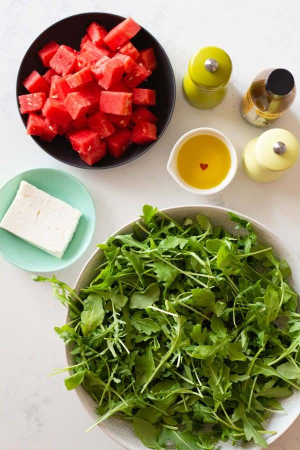 Ingredients for Watermelon Arugula Salad showcased one next to the other
