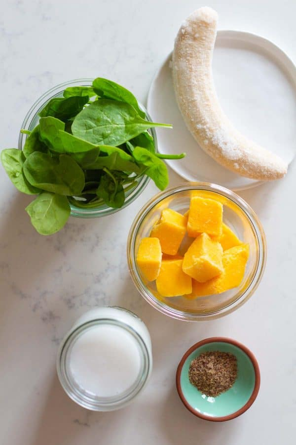 frozen banana, spinach, mango chunks, coconut milk, ground flaxseeds on a kitchen counter