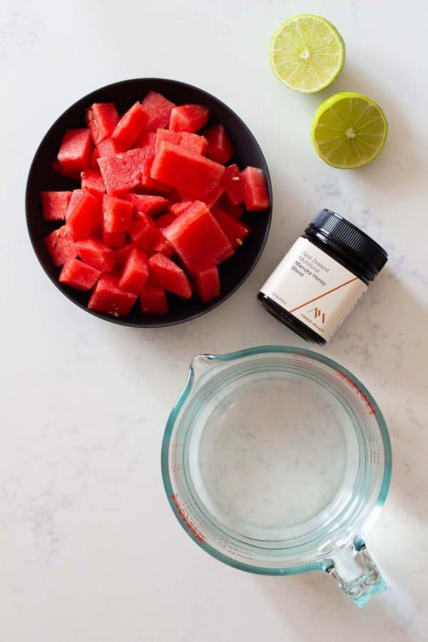 cubed watermelon in a bowl, a jug of water, a lime, and a jar of honey on a kitchen counter