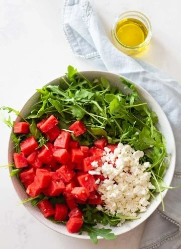 Watermelon and crumbled feta on top of arugula in a salad bowl