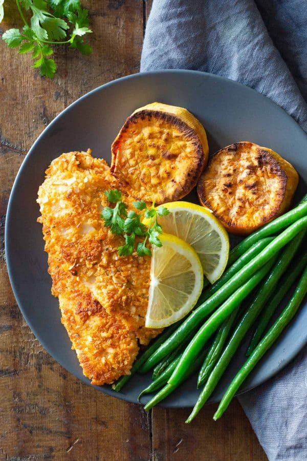 Sole Fish Fillet, sweet potato slices, green beans, and lemon slices on a plate.