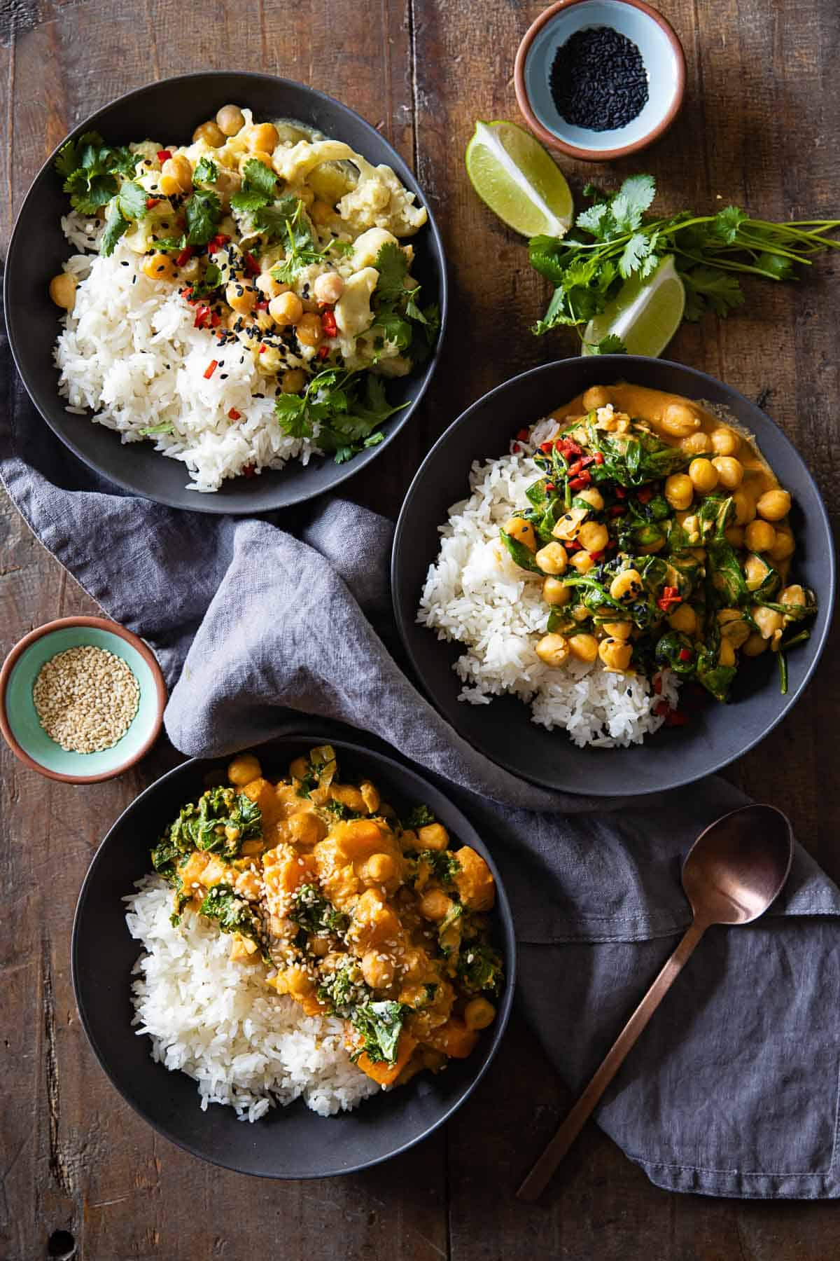 Three bowls with white rice and different kinds of coconut chickpea curry.