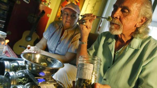 Older Couple with Man Smelling Cannabis