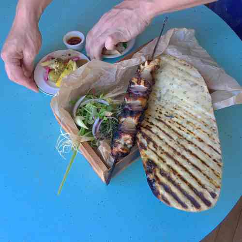 Chicken kebab box, with grilled flatbread, herb salad, tahini, pickled vegetables, and harissa.