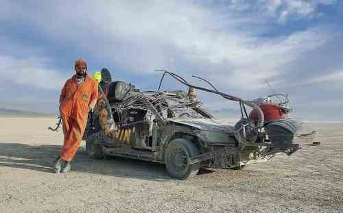 Superchief Gallery LA artist Ryan C. Doyle with his CarCroach at sunrise at Burning Man 2016