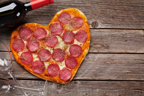 Heart shaped pizza with pepperoni and mozzarella and red wine bottle. Valentines day greeting card. Top view with space for your greetings