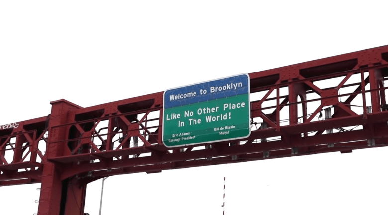 """""""Like No Other Place In The World!"""" reads the sign on the Paluski Bridge welcoming visitors to Brooklyn."""