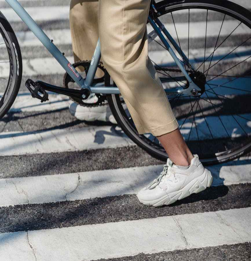 unrecognizable woman riding bicycle on crosswalk