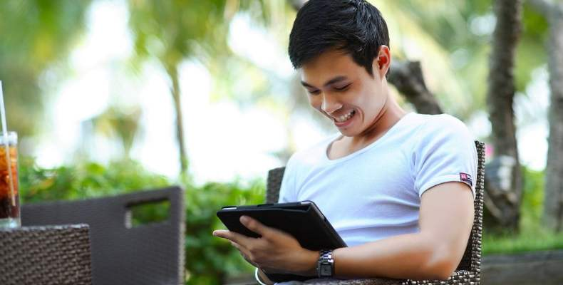 Man Sitting And Using iPad