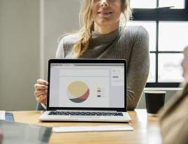 Woman Showing Pie Chart on Laptop