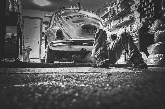 Man Working Under a VW Beetle