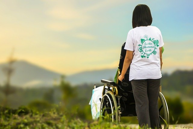 Person in Wheelchair and Caregiver in Field