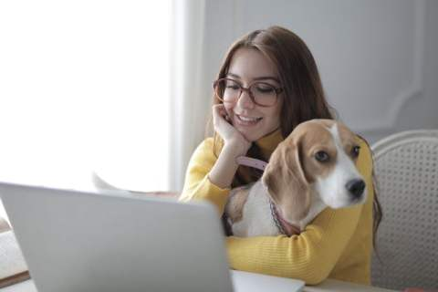 Woman Hugging Dog While Using Laptop